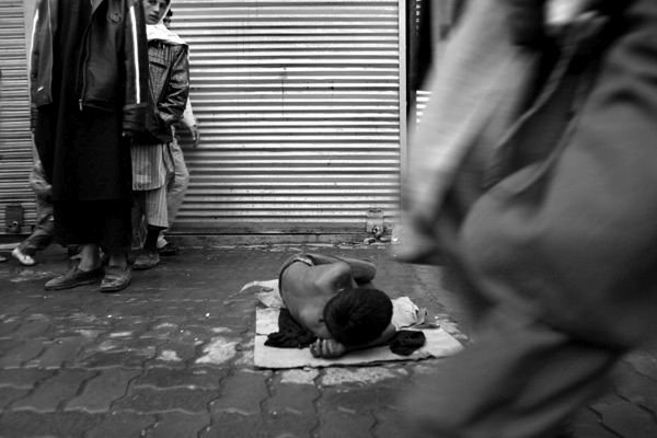 A young boy lays down begging on a busy street in Kabul, Afghanistan.  Due to years of conflict in Afghanistan, thousands of children have been orphaned, with no one to take care of them they beg on the streets or work menial jobs.  October 2006.