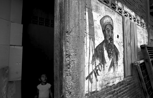 A young girl peers around the corner at the painting her brother did of Osama Bin Ladin on the wall of their home, in Banda Aceh, Indonesia.  February 2007.
