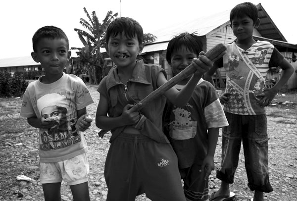 A gang of youth show their bravery by playing soldiers in an internal displacement camp in Banda Aceh, Indonesia.  Though reconstruction is evident everywhere in and around Banda Aceh, many are still living in camps after the devastating tsunami.  It is reported that levels of corruption are high as some families have secured 2-4 homes while others remain homeless.  February 2007.