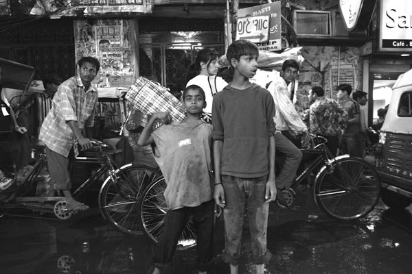 Boys playing and posing for the camera in Par Ganj, Delhi, India.  Though India is now surging economically hundreds of thousands of poor and uneducated make their living by begging from tourists.  One of the most popular streets in Delhi for street kids and touts to work is Par Ganj.  March 2006.