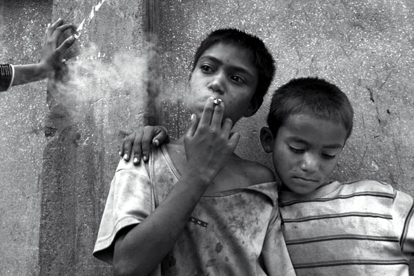 Bikash seen smoking and brother Deepak are street kids in Kathmandu, Nepal.  It is estimated that over 600 children live and work on the streets in the Kathmandu valley.  Most are orphaned, discarded, or escaped their villages when the Maoists tried to recruit them.  June 2005.
