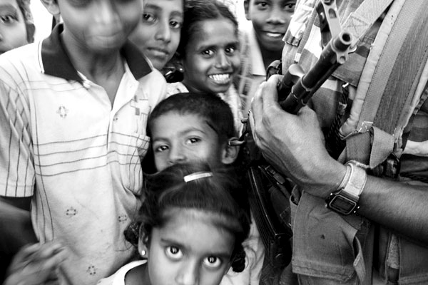 Children play around Sri Lankan army guards while waiting to be transferred to a new internally displacement camp one month after the tsunami in Batticaloa, Sri Lanka.  This area is Tamil Tiger controlled and received very little of aid promised by the donors or government.  February 2005.