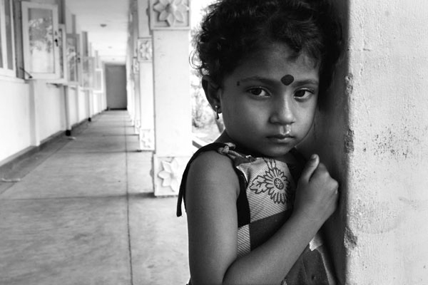 A young girl in a displacement camp in Batticaloa, Sri Lanka.  One month after the tsunami took her family, she could neither speak nor play, rather she spent her time staring out to the road waiting.  March 2005.