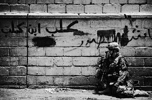 A soldier rests on the streets of Sadr City, Iraq during a dismounted security patrol June, 2008.  Most soldiers and Marines work over ten (and up to 20 or more) hours a day, seven days a week in temperatures reaching 60c/140f.  To add to the physical stress, body armor weighs around 18kg/40lbs and combined with other equipment they often carry a total of 31kg/70lbs.  The mental stress also weighs on soldiers and Marines, as most of their time outside of bases is spent trying to guess who may be friendly and who may be their enemy.